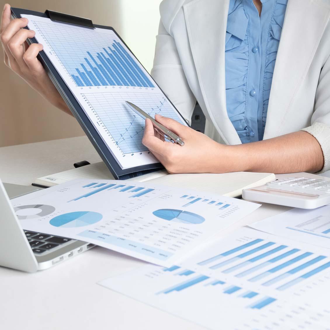 Imagem em close de uma mulher apresentando gráficos de reatórios