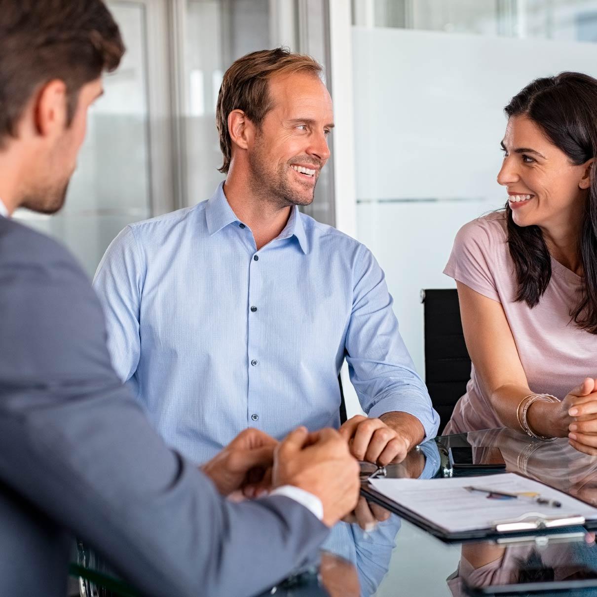 Um homem e uma mulher sorriem um para o outro na mesa durante uma reunião. Um segundo homem de negócios está de costas para a câmera.