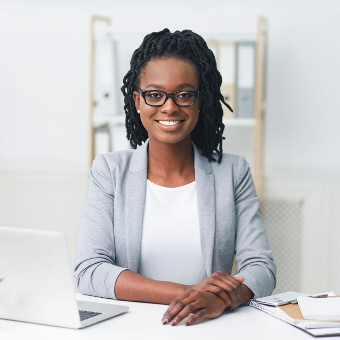 Uma mulher de negócios sorri enquanto olha para a câmera.