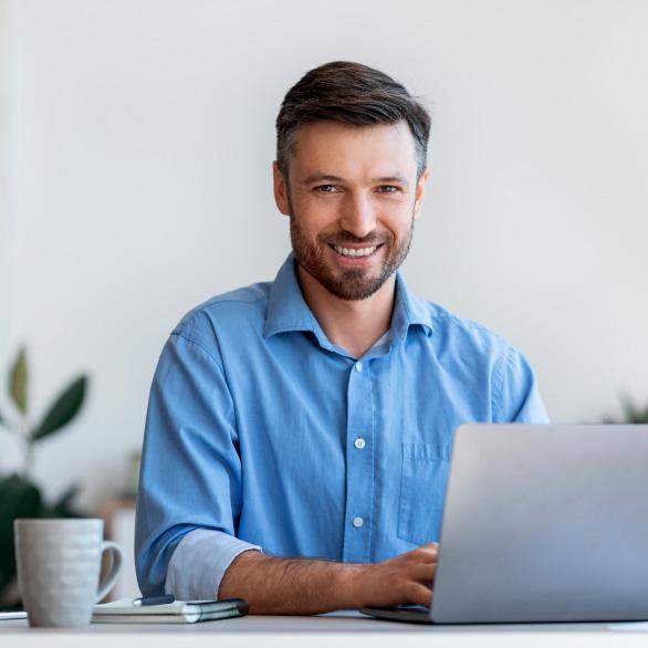 Um homem de negócios sorri para a câmera enquanto trabalha em seu notebook